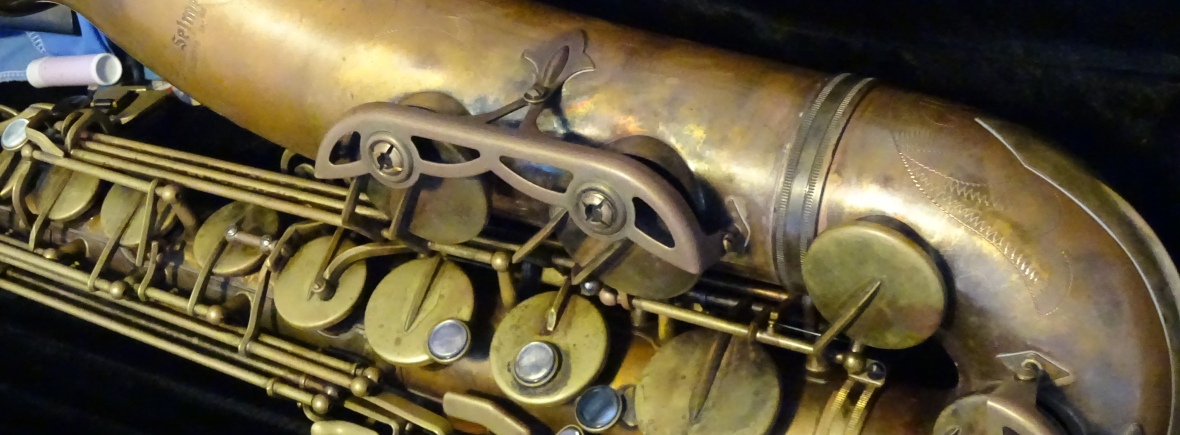 A side view of a Conn-Selmer Premiere Tenor saxophone with a 'Vintage' lacquer. The neck from the top of the bell up is not visible. The sax is resting in it's case. A cleaning cloth, stick of cork grease and reed case are visible in the top left hand corner.