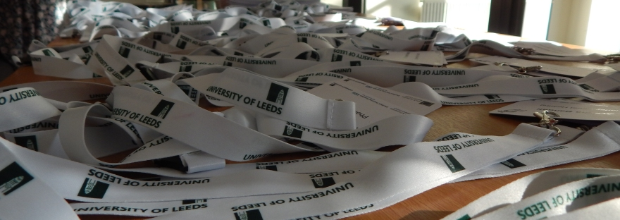 A close-up photo of a table holding a large number of white lanyards. The lanyards have the 'University of Leeds' logo printed on them in dark green.