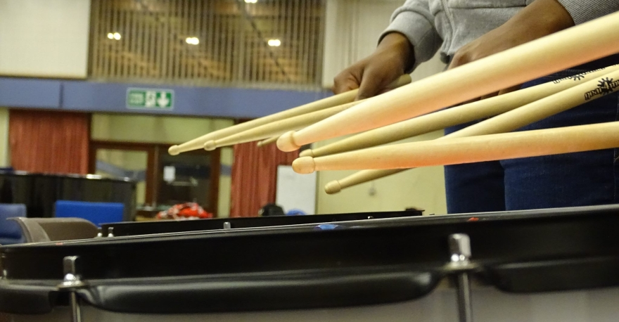 The bottom of the photo is a close up of the rim of a marching snare drum. The rim of a second drum is visible behind the first. The hands and of someone wearing a grey hoodie and blue jeans are holding a set of drumsticks over the back drum. in fron of this person there are two more pairs of sticks being held over the line of drums though the holders are not visible.