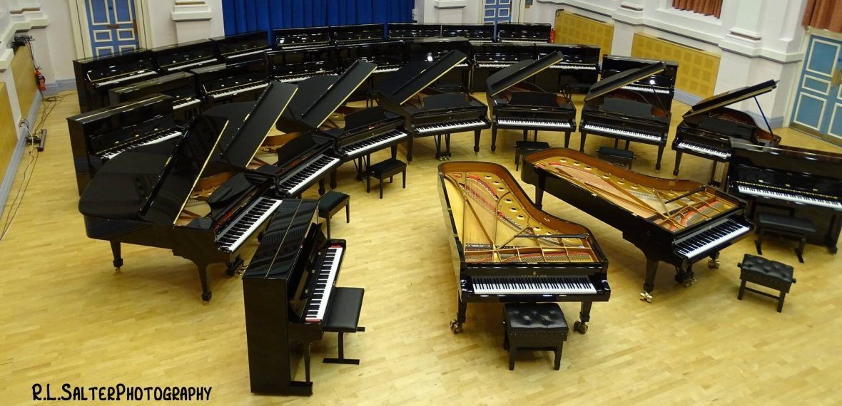 A landscape photo of the clothworker's centenary concert hall at the University of Leeds. The hall contains 27 Steinway pianos: 2 concert grands, 7 baby grands, and 18 uprights